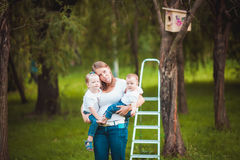 Mother and her daughters with Wooden birdhouse Stock Images