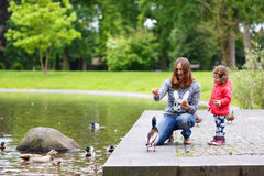Mother and her daugther feeding ducks at summer. Mother and her adorable daughter girl feeding ducks at summer, in park royalty free stock image