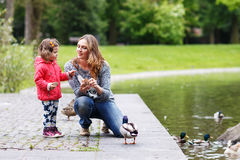 Mother and her daugther feeding ducks at summer. Mother and her adorable daughter girl feeding ducks at summer, in park stock photography