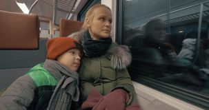 Mother and her gentle loving son traveling by train. Boy kissing mom and cuddling with her while traveling by commuter train in late winter evening. Both tired stock footage