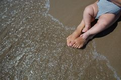 Mother and her infant son wash their legs in the sea Stock Photo
