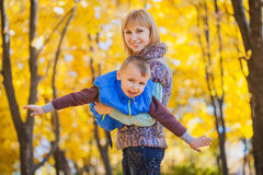 Mother and her kid have fun in the autumn park Stock Photography