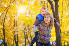 Mother and her kid have fun in the autumn park Royalty Free Stock Images