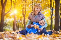 Mother and her kid have fun in the autumn park Royalty Free Stock Photo
