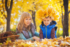 Mother and her kid have fun in the yellow leaves Royalty Free Stock Image