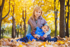 Mother and her kid have fun in the yellow leaves Stock Photo