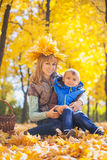 Mother and her kid have fun in the yellow leaves Royalty Free Stock Photography