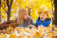 Mother and her kid have fun in the yellow leaves Royalty Free Stock Photo