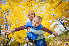 Mother and her kid have fun in the yellow leaves Stock Image