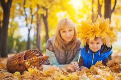 Mother and her kid have fun in the yellow leaves Stock Images