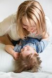 Mother and her kid lying on the bed and smiling Stock Images