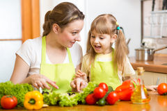 Mother and her kid making vegetable salad Stock Photos