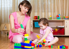 Mother and her kid play with block toys at home Stock Photos