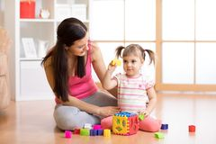 Mother and her kid playing with colorful logical sorter toy. Mother and her kid girl playing with colorful logical sorter toy Royalty Free Stock Image