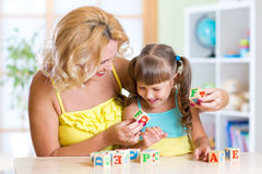 Mother and her kid playing with cubes and learning Royalty Free Stock Photos