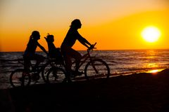 Mother and her kids on the bicycle silhouettes. On beach at sunset royalty free stock photography