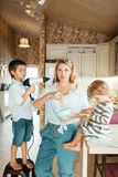 Mother and her kids cooking pastry with chocolate stock photo