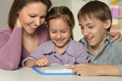 Mother with her kids. Doing homework at home Royalty Free Stock Photo