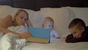 A mother and her kids having family time before bed. A mother and her kids are watching something on a tablet, while lying on a large bed. A young woman is stock video footage