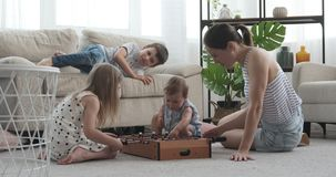 Mother with her kids having fun. Playing foosball at home stock video
