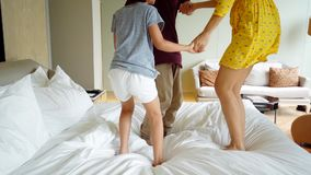 Mother and her kids jumping on bed. Feet of unknown mother and her kids jumping on the bed while holding hands in the hotel room stock footage