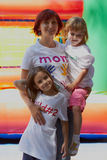 Mother with her kids outdoors. Young mother embracing her kids outdoors with the bouncing castle on the background Stock Images