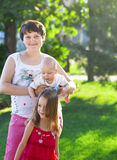 Mother and her kids outdoors. Happy mum and her children playing Stock Images