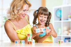 Mother and her kids playing with cubes Royalty Free Stock Image