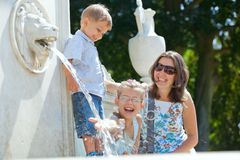 Mother with her kids playing with water. Beautiful Mother with her kids playing with water in fountain Stock Photo
