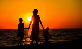 Mother and her kids silhouettes. On beach at sunset stock photo