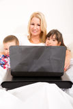 Mother with her kids using a laptop in bed Royalty Free Stock Photography
