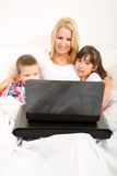 Mother with her kids using a laptop in bed Royalty Free Stock Images