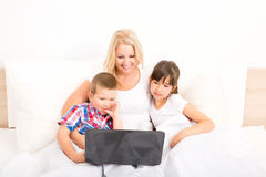 Mother with her kids using a laptop in bed Stock Photos