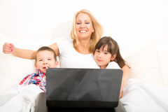 Mother with her kids using a laptop in bed Royalty Free Stock Photo