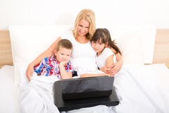 Mother with her kids using a laptop in bed Stock Image