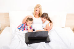Mother with her kids using a laptop in bed Royalty Free Stock Image