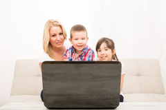 Mother with her Kids using a Laptop computer Stock Photo