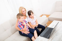 Mother with her Kids using a Laptop computer Royalty Free Stock Image