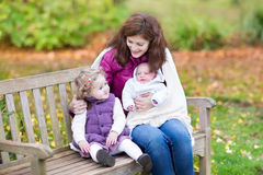Mother with her kids on wooden bench in park. Young mother relaxing on a wooden bench in a colorful autumn park with her toddler daughter and newborn son covered Stock Photography