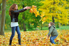 Mother and her little child having fun in a park Stock Photos