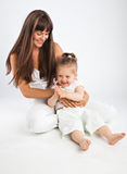 Mother and her little daughter. Gray background Royalty Free Stock Photography