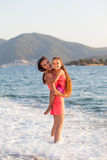 Mother and her little daughter on the beach during sunset Royalty Free Stock Photo