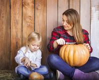 Mother and her little daughter carving Halloween pumpkins Stock Photos