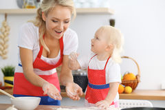 Mother and her little daughter cooking holiday pie or cookies for Mother`s day. Concept of happy family in the kitchen royalty free stock photo