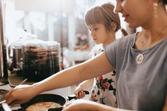 Mother and her little daughter cooking pancakes for the breakfast in the little cozy kitchen royalty free stock photography