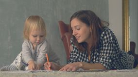 Mother and her little daughter are drawing with pencils in album stock footage