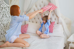 Mother with her little daughter fight by a pillows on a bed. Mother with her little daughter fight by a pillows on bed Stock Photo