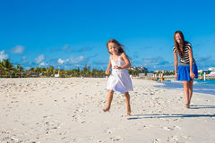 Mother and her little daughter having fun at exotic beach on sunny day Stock Photo