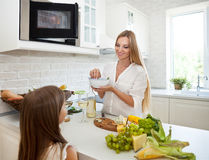 Mother and her little daughter in the kitchen Royalty Free Stock Photography