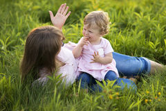 Mother  with her little daughter on a meadow, explaining something Stock Photography